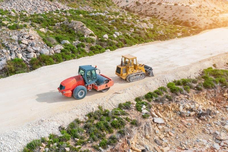 Rouleau et excavatrice sur un chemin de terre avant d'étendre l'asphalte, vue aérienne images libres de droits