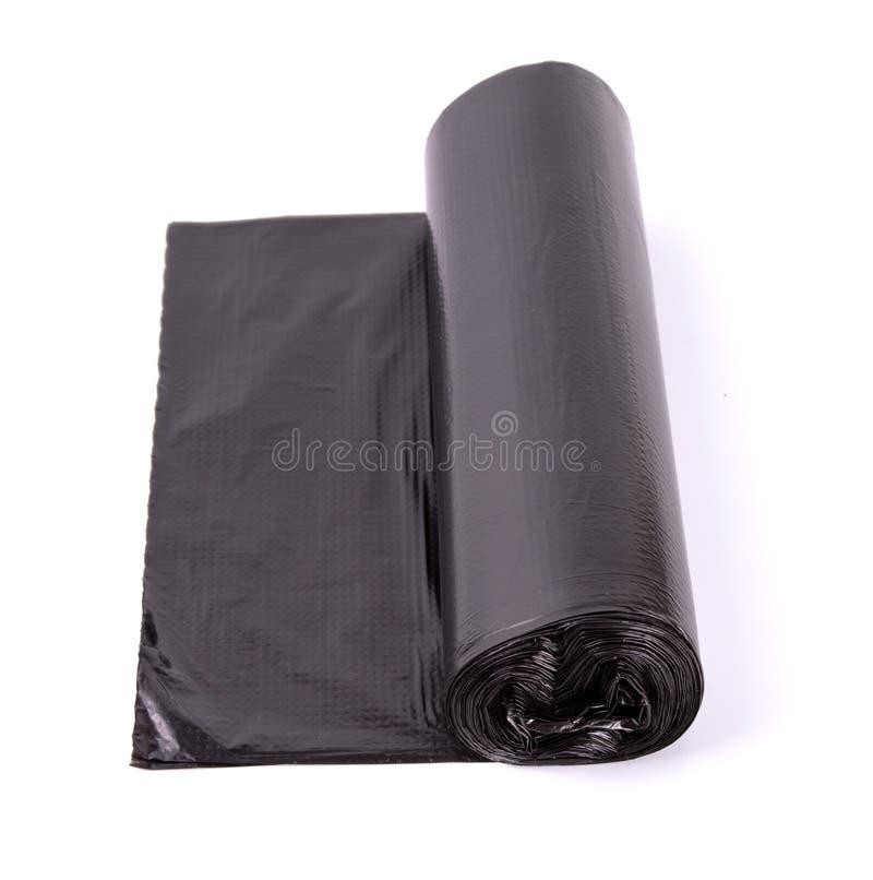 Rouleau noir de sacs de déchets en plastique d'isolement sur le fond blanc photographie stock libre de droits