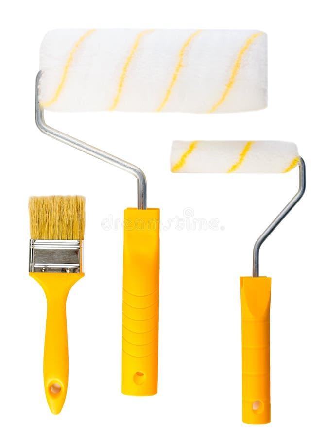 Rouleaux jaunes de pinceau et de peinture d'isolement images stock