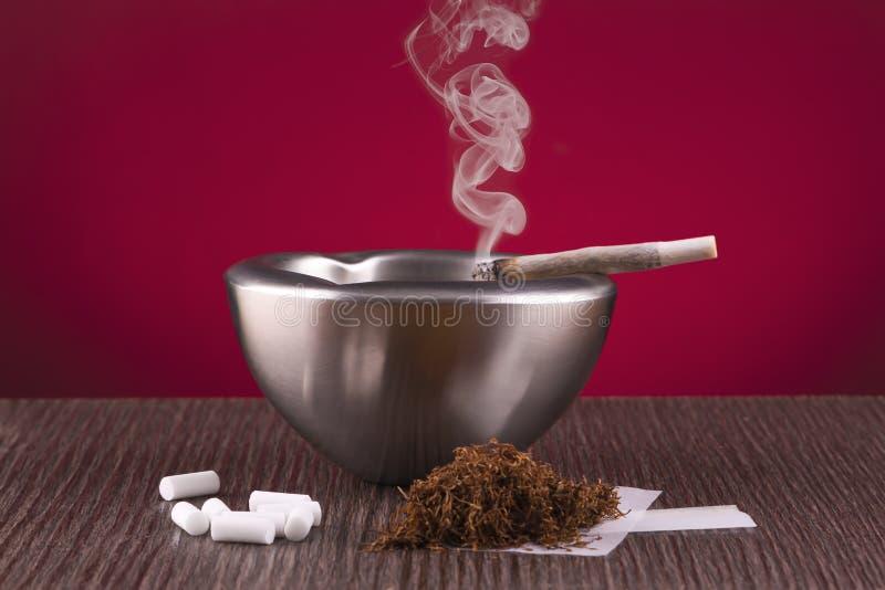 Roulement, cendrier et cigare de tabac à priser photographie stock