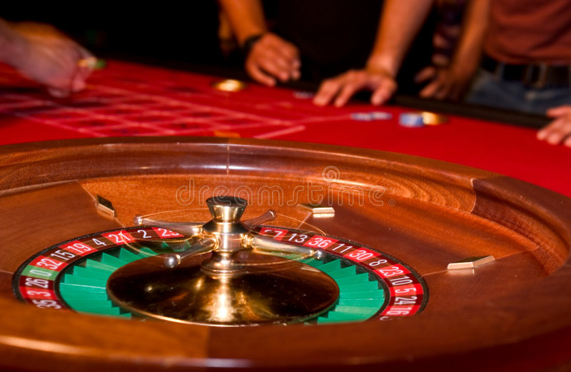 Roulette. Wheel with gamblers in the background