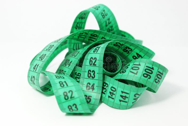 Roulette sottili verdi su un fondo bianco I nastri di misurazione adattano con gli indicatori digitali immagini stock libere da diritti