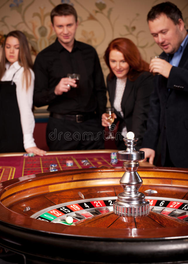 Roulette table with people on background stock image