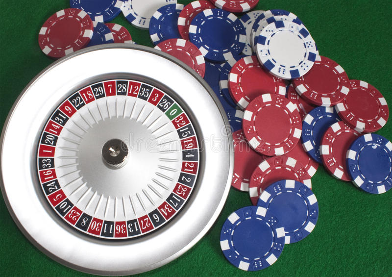 Roulette wheel and chips on green beize. Poker chips scattered around a roulette wheel stock photography
