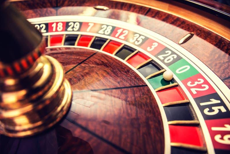 Rouletten rullar i kasino med bollen på den nollgröna positionen royaltyfri foto