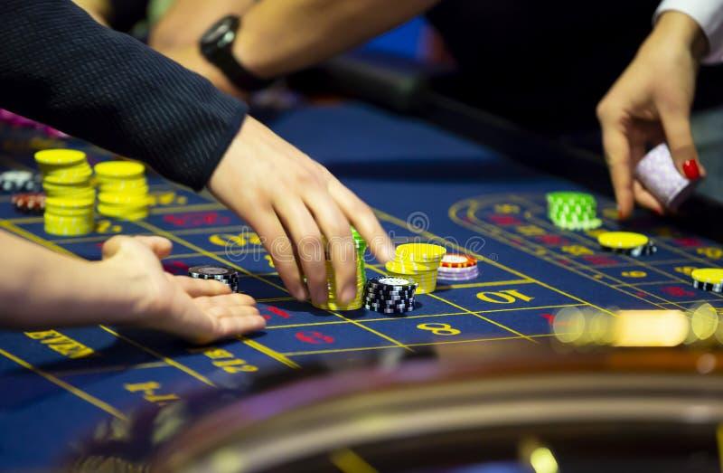 Rouletttabell i mänskliga händer för kasino arkivfoto