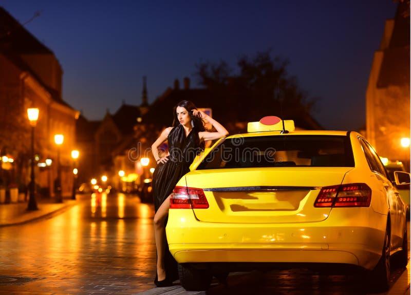 Roulez au sol la voiture et la jolie femme dans la robe de soirée roulez au sol la voiture pour la belle femme dans la robe éléga photo libre de droits