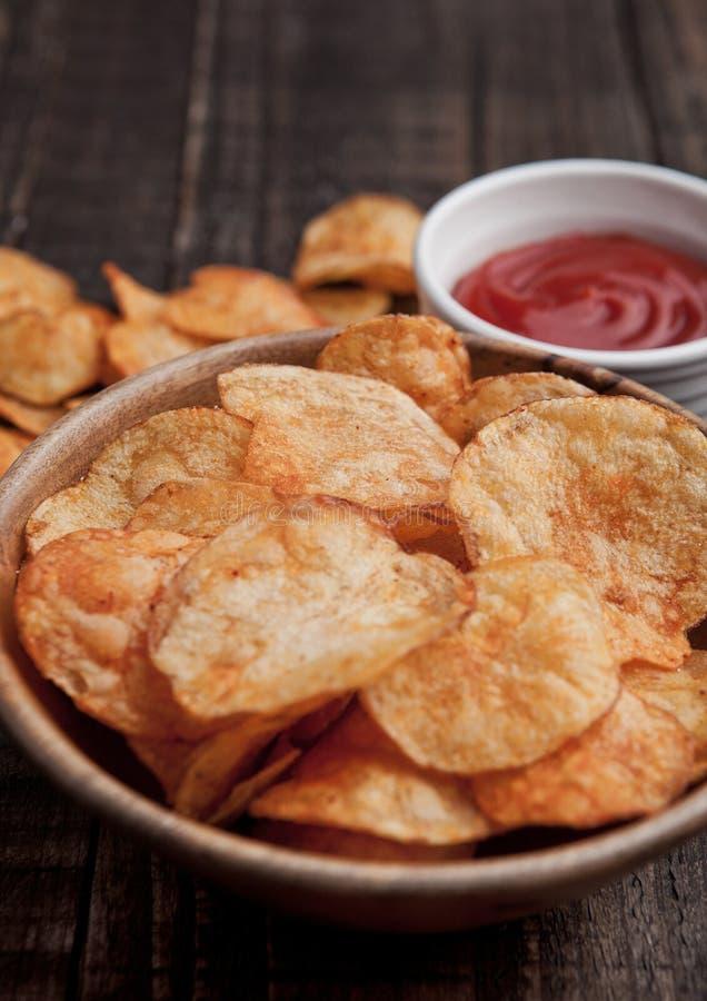 Roulez avec les frites et le ketchup de pommes chips sur le conseil en bois photographie stock libre de droits