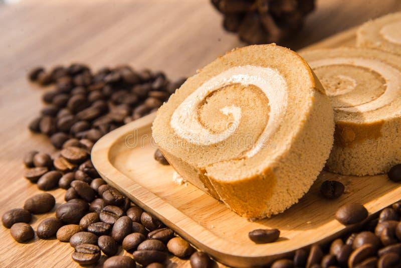 Roulez le gâteau au café et le grain de café avec du Li en bois de table et de fenêtre photographie stock libre de droits