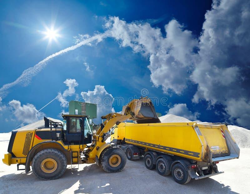Roulez les charges de chargeur un camion avec le sable dans un puits de gravier image stock