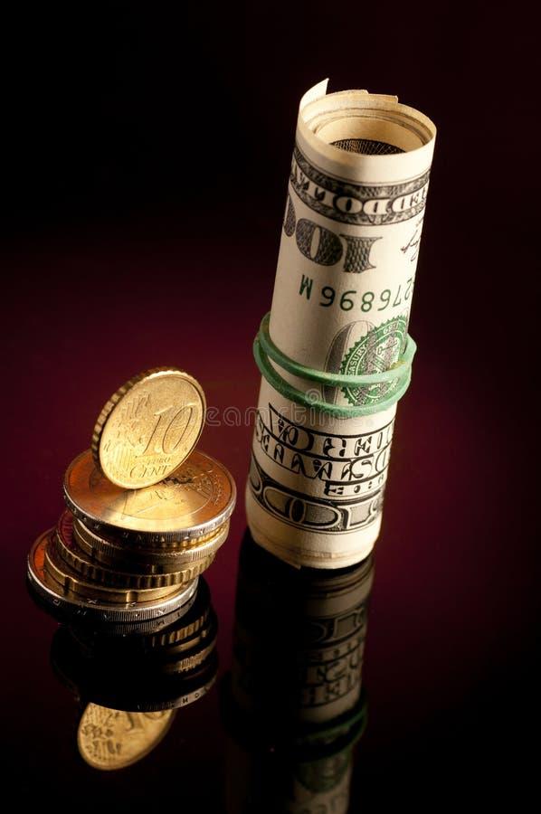 Roulis d'argent avec des dollars US, Et euro pièces de monnaie image stock