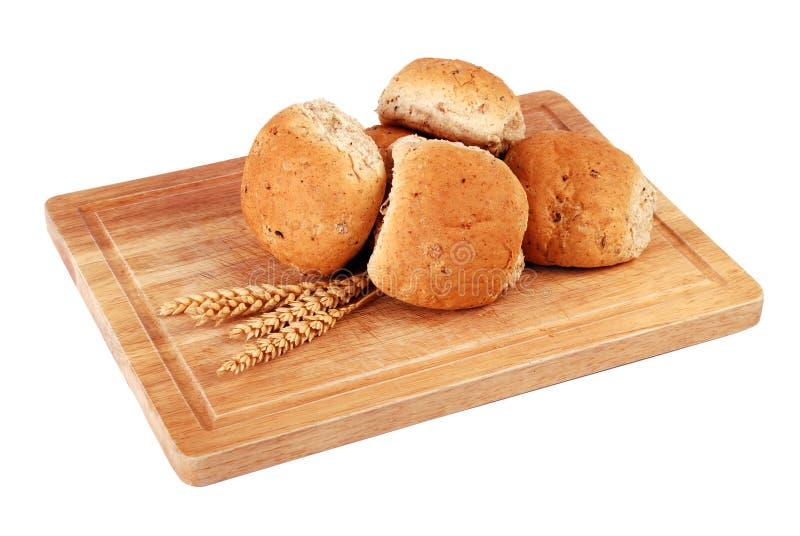 Roulis de pain sur un panneau en bois images libres de droits