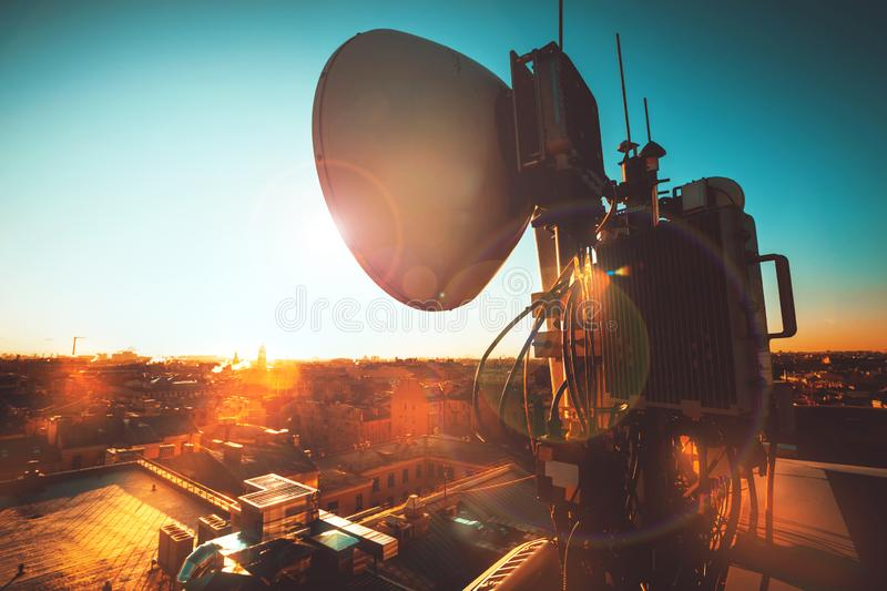 The round antenna on the roof of a building in the city at sunset royalty free stock images