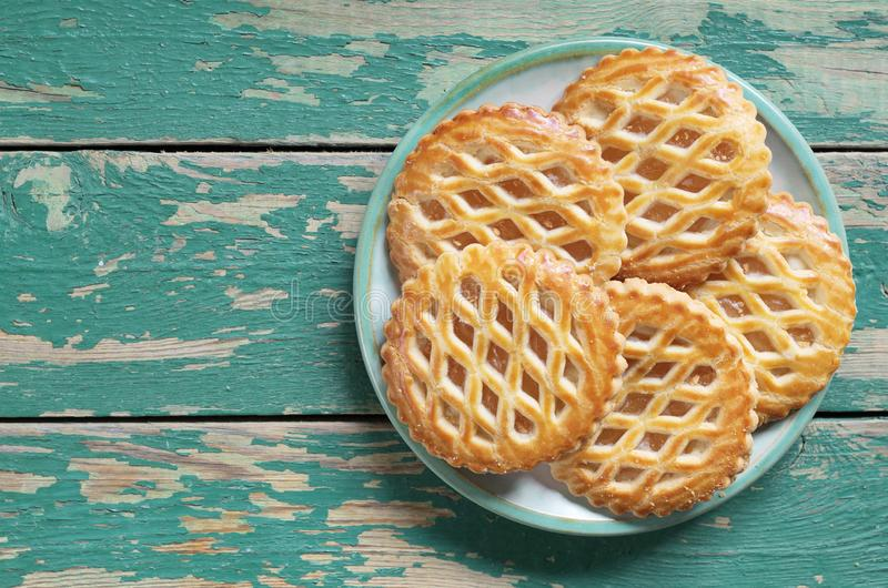 Round Apple Lattice Cakes in plate. On old wooden background, top view with copy space stock image