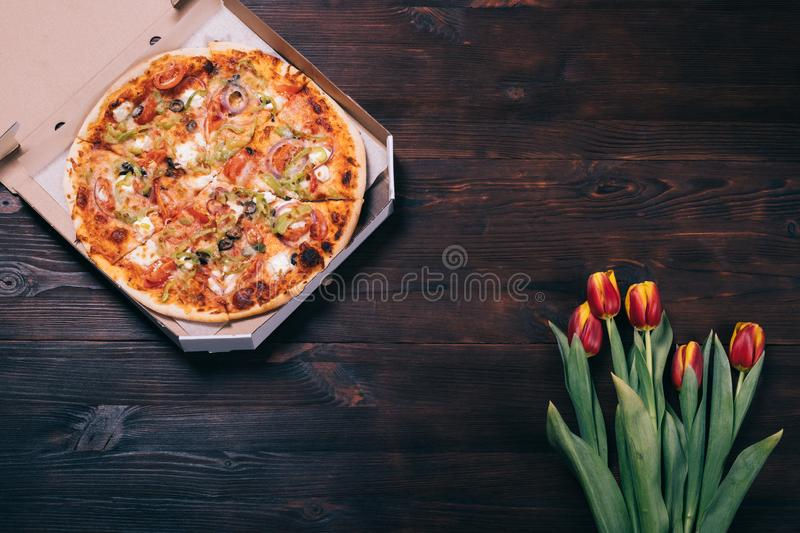 Round baked pizza in cardboard box on dark brown wooden table. Near bouquet of fresh red-yellow flowers tulips, top view stock photography
