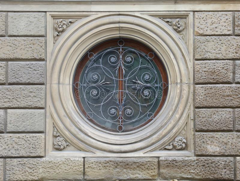 Round barred window. Round window closed by an openwork barrier royalty free stock image