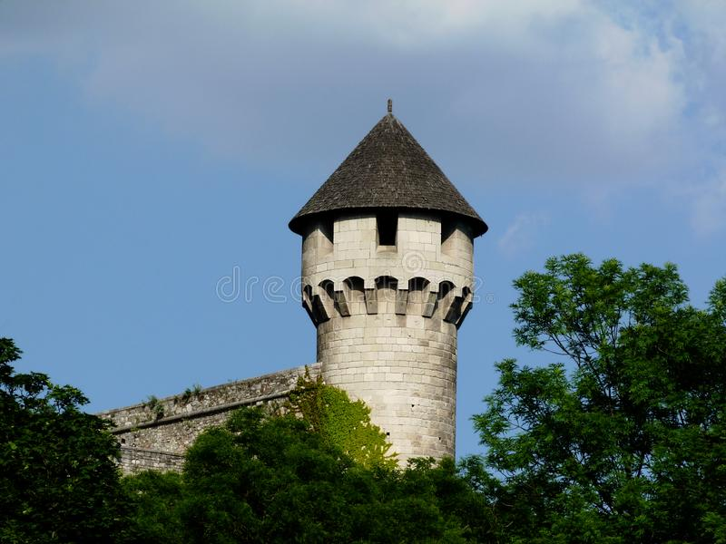 Stone stone tower and turret with wooden shingle sloped roof. Round base stone tower and turret with wooden shingle steep sloped roof. spring trees with lush royalty free stock images