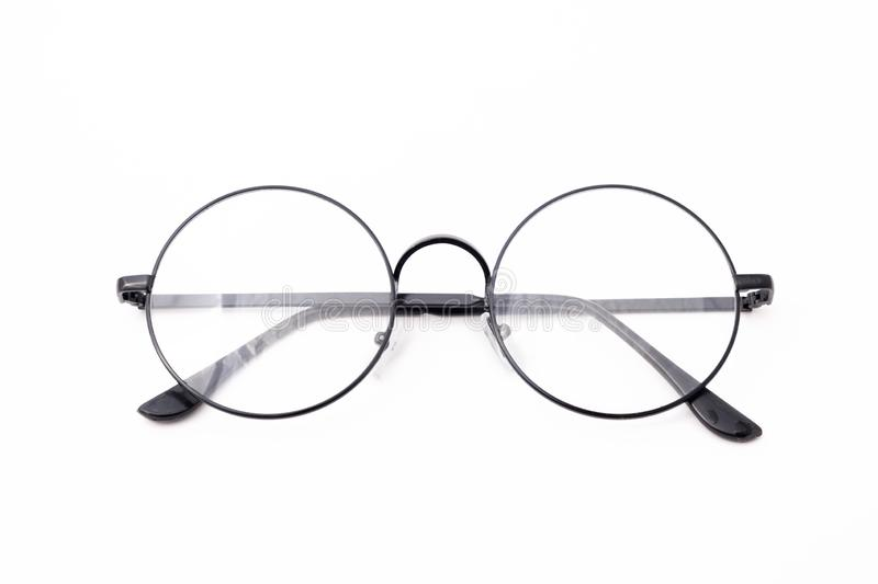 Round black-rimmed glasses are located frontally on a white background. Isolated. eyeglasses points folded in the back royalty free stock images