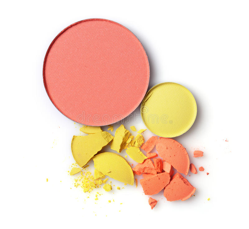 Round blusher with yellow and orange crashed eyeshadow for makeup as sample of cosmetics product stock images