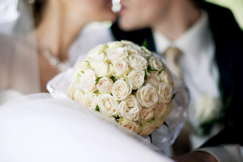 Round bouquet of white roses on a background of kissing newlyweds royalty free stock image