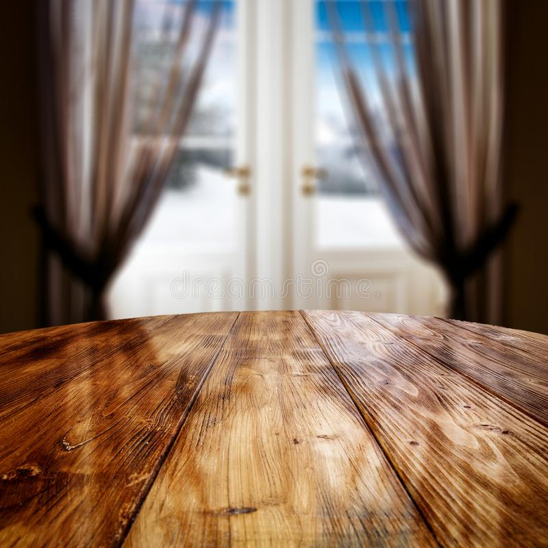 Round brown wooden table top with empty space for products and decorations. Blurred window background. Brown curtains in a big window. Blurred view garden stock image