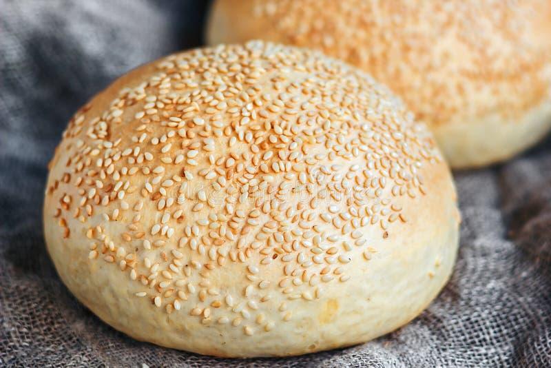 Round bun, sesame bun, bread rolls. Tasty burger bread with sesame on wooden, burlap background. Freshly baked hamburger buns. Top. View stock images