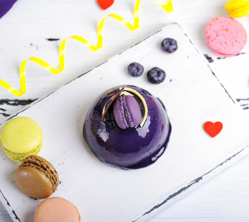 Round cake with lilac fondant and decor. On a white board, vintage toning, beside colored pastry macarons, top view royalty free stock photography