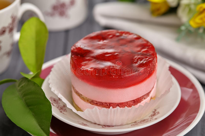 Round cake with raspberry jelly and cream. Cake in a plate on the wooden table, flowers and a cup of tea royalty free stock photos