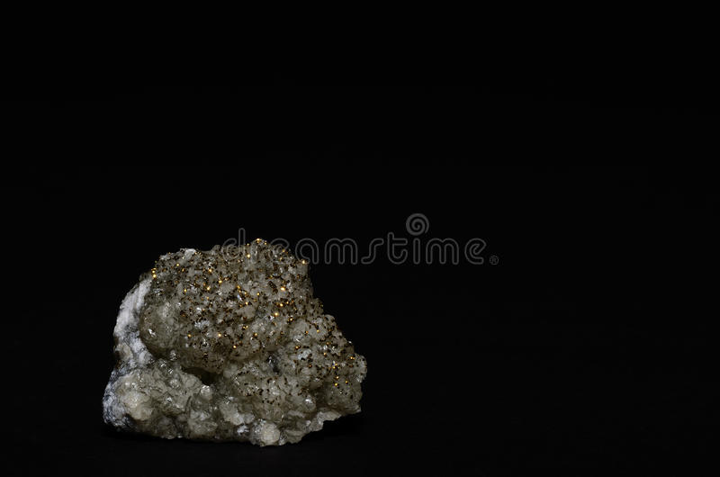 Round calcite pyrite pieces and black. Round calcite stone with pyrite pieces and black background stock photography