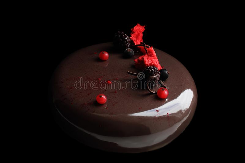 Round chocolate cake with berries and red sponge on black background royalty free stock image