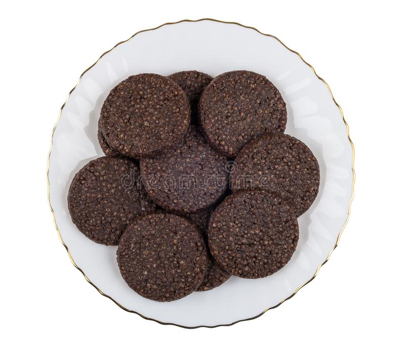 Round chocolate cookies with airy rice in plate on white. Round chocolate cookies with airy rice in glass plate isolated on white background. Top view stock image