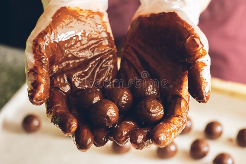 Round chocolates doused with liquid chocolate in the hands of the confectioner chocolatier. Making handmade chocolates. Making handmade chocolates. Round royalty free stock image