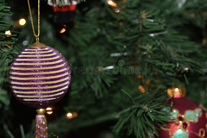 Striped Christmas ornament hanging in tree. Round Christmas ornament hanging onto a Christmas tree. A Colorful handmade design royalty free stock image