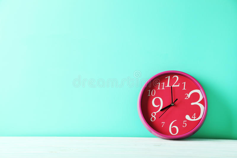 Round clock. Pink round clock on a green wooden table stock photos