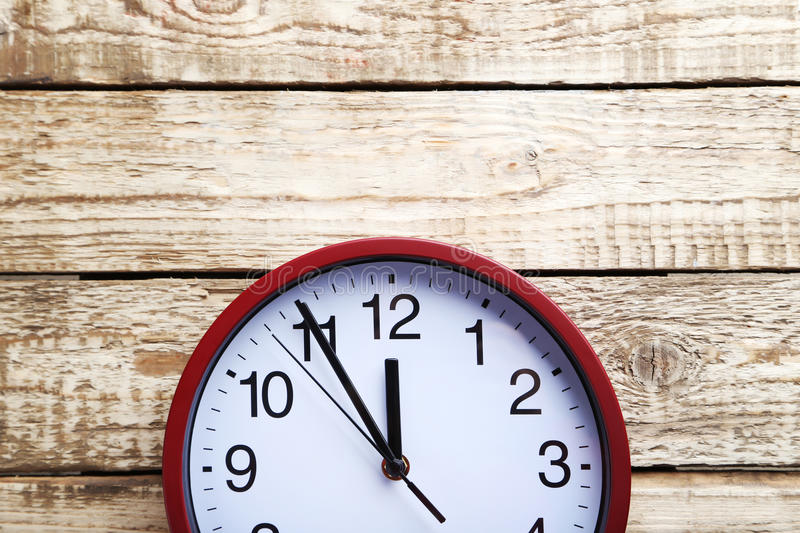Round clock. Red round clock on a grey wooden table stock photos