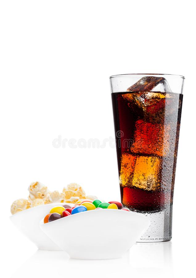 Round coated sweet candies with cola and popcorn. Round colorful coated sweet candies and popcorn in white bowl with cola soda drink on white background stock image