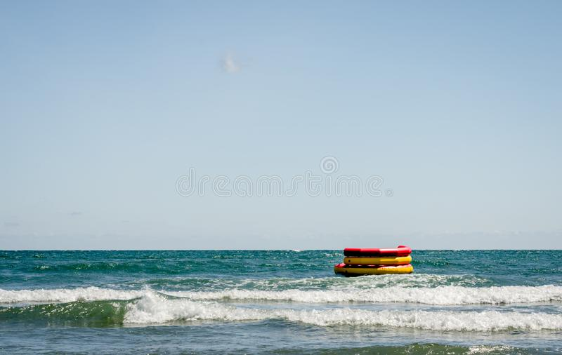 Round colorful inflatable boat ready for fun  on water  near sheashore royalty free stock photos