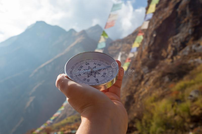 Round compass in hand on the background of blurred mountain and prayer buddhist flags fluttering in the wind. Concept for travelling and active lifestyle stock photos