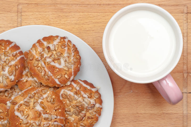 Round cookies with sunflower and sesame seeds, milk in pink mug, top view. Valuable breakfeast. stock photography