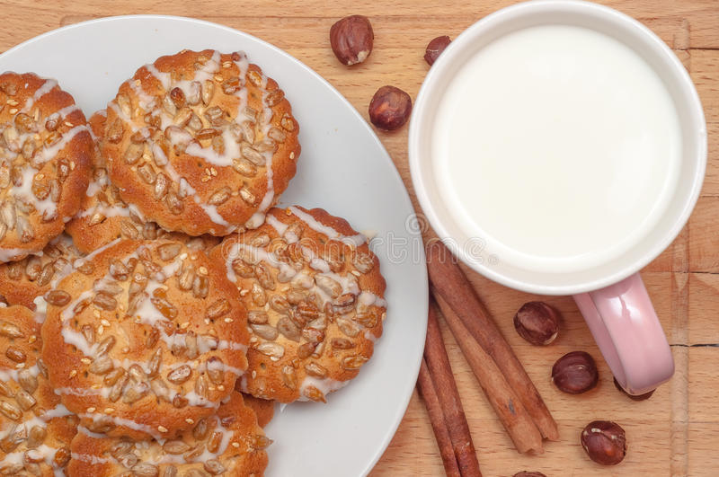 Round cookies with sunflower and sesame seeds, milk in pink mug, top view. Valuable breakfeast. royalty free stock photo