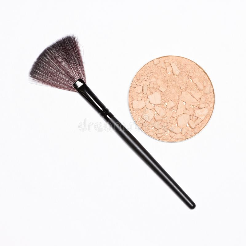 Crushed compact powder with fan make-up brush. Round cosmetic container of crushed compact powder with fan make-up brush on white background, copy space stock photos