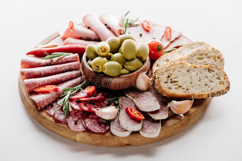 Round cutting board with delicious salami, ham, olives in bowl, bread, herbs, tomato, chili and garlic cloves. On white table stock photos
