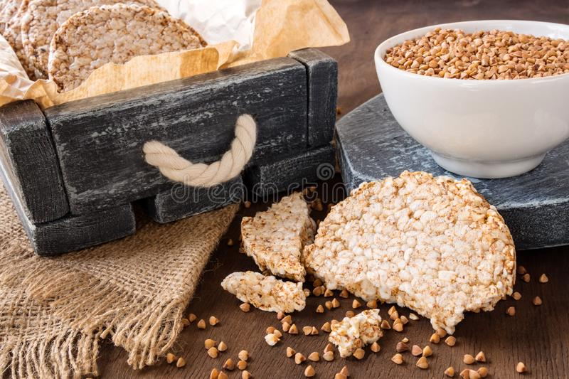 Round dietary loaves of airy buckwheat  in vintage box and a cup of raw buckwheat on wooden background royalty free stock photography