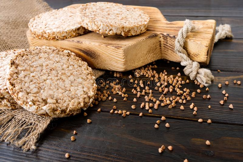 Round dietary loaves of airy buckwheat  on wooden background with buckwheat scattered around, vintage board and burlap stock image