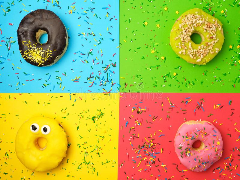 round different donuts with sprinkles on a bright multi-colored background stock photo