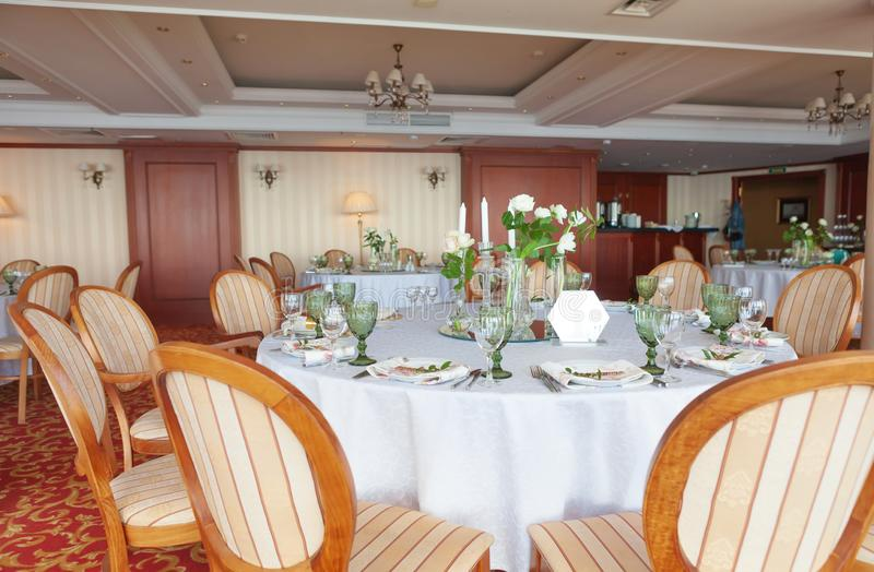 Round dining tables, covered with white cloth, served with green glasses and ornate with flowers, stand on a colored carpet. Close stock photography