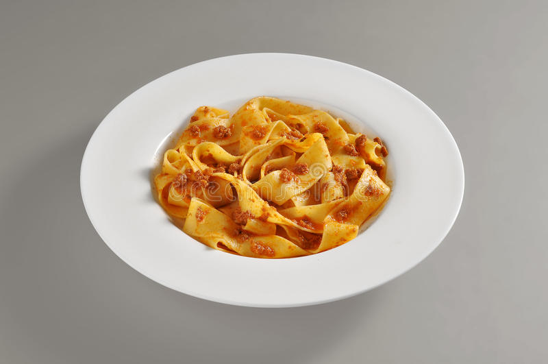 Round dish with a serving of pappardelle pasta with meat souce stock photography