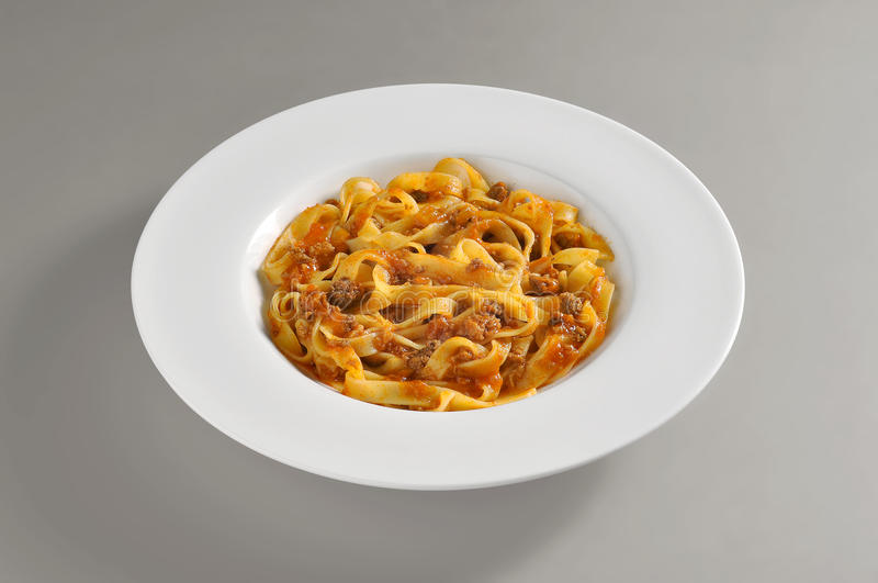 Round dish with a serving of tagliatelle pasta with meat souce royalty free stock photography