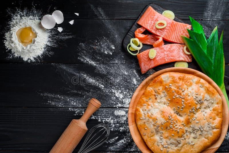 Round domowej roboty łososiowy kulebiak na czarnym drewnianym tle w pięknym składzie Odg?rny widok przestrze? Zako?czenie zdjęcia royalty free