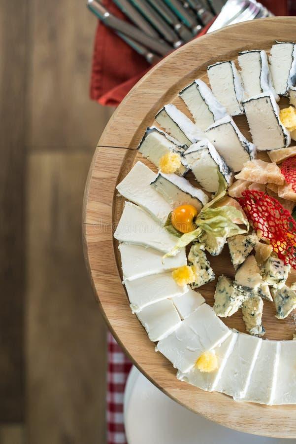 Round drewniany talerz z różnymi rodzajami ser i miód Odgórny widok obrazy royalty free